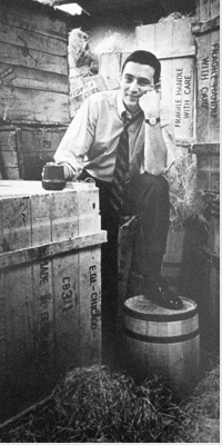 Photo of Gordon Segal surrounded by crates and barrels.